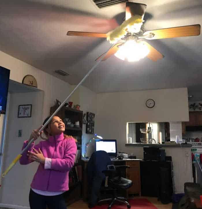 girl dusting ceiling fan with Swiffer duster