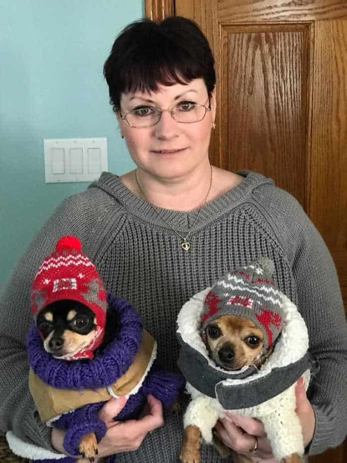 woman holding 2 chihuahuas in winter coats
