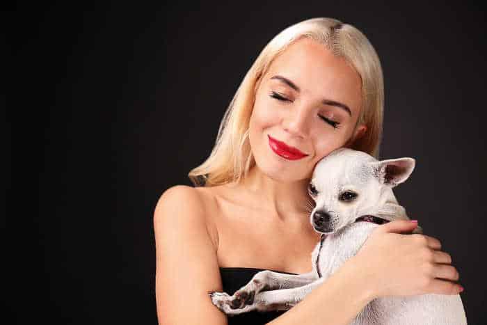 blond woman hugging chihuahua