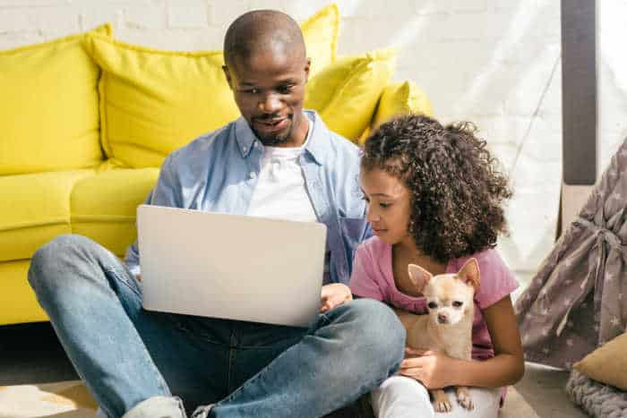 black father and daughter with laptop holding chihuahua